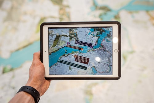 Person holding up a tablet showing augmented reality