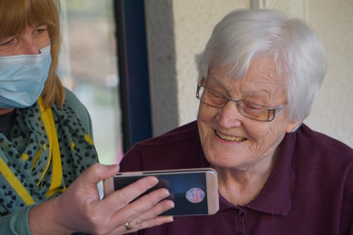 elderly woman looking at a phone held up by a carer