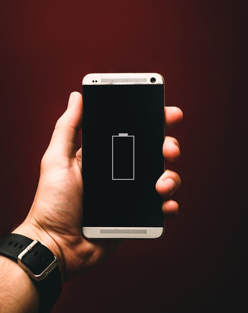 Person holding up a phone which displays a depleted battery on the screen