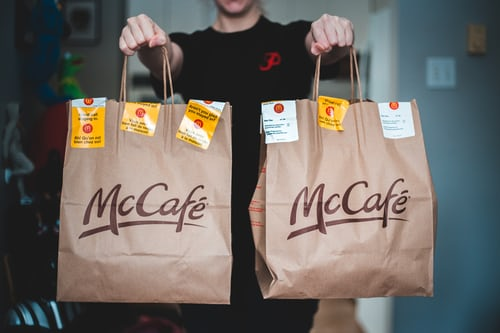Person holding McDonald's McCafe food bags